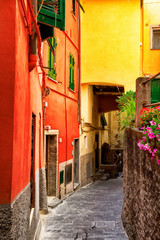 Bright old street with colorful architecture in Riomaggiore, Cinque Terre, Italy. Narrow lane.