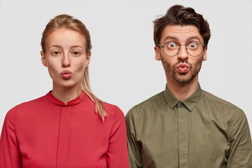 People, friendship and facial expressions concept. Lovely young female model in red blouse stands near hipster male, keep lips round and make grimace while being photographed for youth magazine © Wayhome Studio