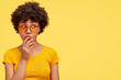 Pretty young dark skinned female contemplates about something and looks mysteriously aside, wears casual yellow t shirt and fashionable shades, isolated over blank wall. Monochrome, one tone