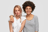 Two female mutiethnic lesbians embrace each other and smile joyfully, pose at camera with happy expressions, isolated over white background. African American woman hugs her European companion - 208516723