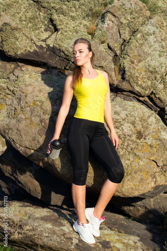 Plakat Young beautiful woman relaxing with water in hands after doing sport exercises outdoors