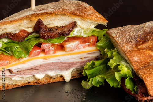 Close up of the cut side of a club sandwich oozing with sauces