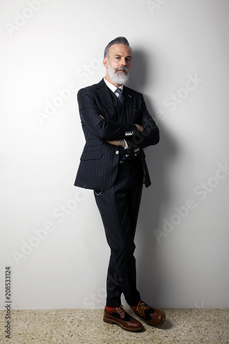 Leinwanddruck Bild Portrait of confident bearded middle aged gentleman wearing trendy suit standing over empty white background. Studio shot. Vertical
