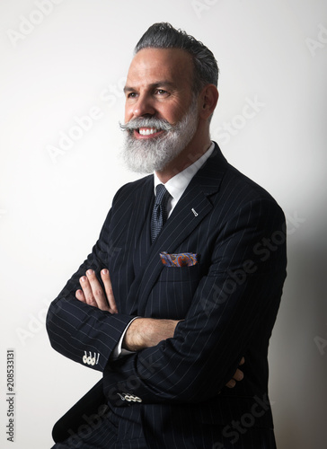 Portrait of positive bearded middle aged gentleman wearing trendy suit over empty gray background. Studio shot. Vertical