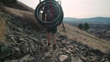 Hiker with a bike and oars on their back walks across rocks on hill - 208533717