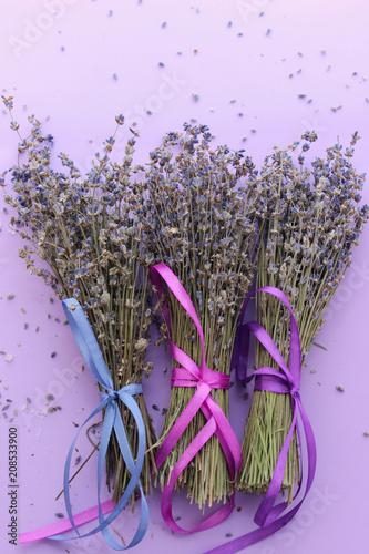 Fotobehang Lavendel Bundles of dried lavender bandaged with ribbon on purple background, top view