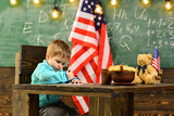 Back to school or home schooling. Little boy in classroom with American flag at knowledge day. Patriotism and freedom. Happy independence day of the usa. School kid at lesson in 4th of july