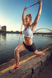 Young fitness woman doing workout with rubber band on the wall by the river in a sunset. - 208539536