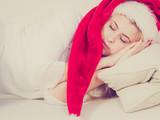 girl wearing santa hat sleeping on sofa at home - 208539545
