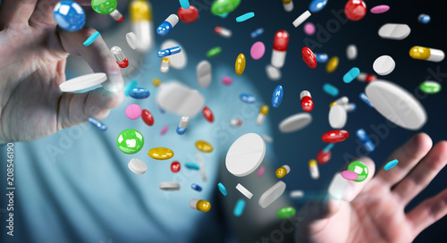 Businessman holding and touching floating medicine pills 3D rendering - 208546190