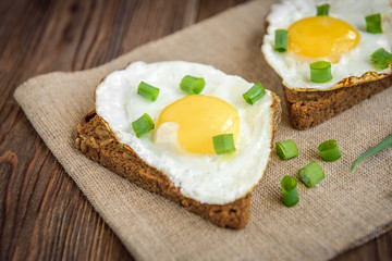 Toast with fried eggs and spring green onion on dark wooden background. Healthy breakfast, lunch, snack or dinner.