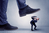 Young handsome businessman getting crushed by a big formal shoe  - 208549703