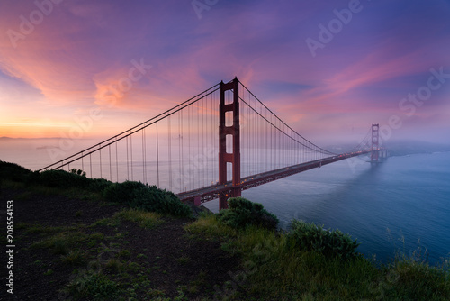 Fotobehang San Francisco Golden Gate bridge during sunrise with the city view background