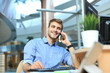Leinwanddruck Bild - Smiling businessman sitting and using mobile phone in office.
