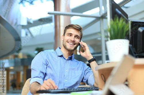 Leinwanddruck Bild Smiling businessman sitting and using mobile phone in office.