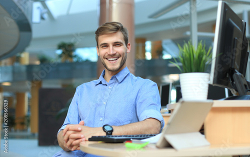 Portrait of happy man sitting at office desk, looking at camera, smiling. - 208566329