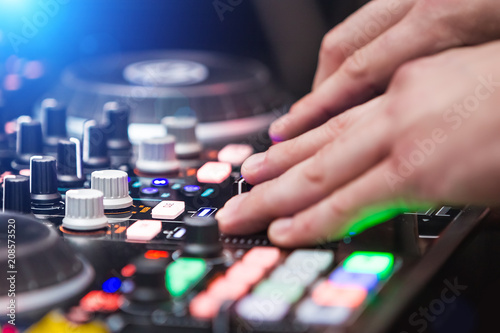 closeup hands of DJ at the turntable wearing white shirt. disc jockey playing on the best, famous CD players at night club. party clubbing life concept
