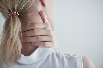 Osteochondrosis. Back pain. Girl holds hand to neck © amixstudio