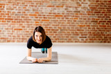 Charming young woman doing push up exercise  in modern loft interior. - 208583156