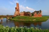 Fototapeta Room - Pejzaż z malowniczymi ruinami zamku w Besiekierach, Polska, na zielonej wysepce otoczonej fosą z wodą, drewniany pomost, roślinność, pogodny letni dzień, błękitne niebo © Wioletta