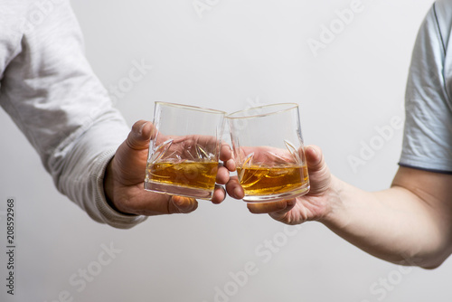 Two men clanging glasses of alcoholic beverage together while