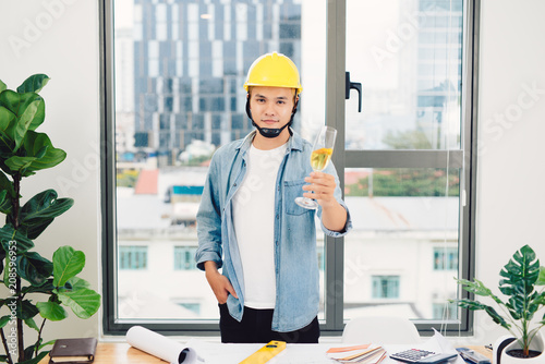 Poster Architect sketching construction project on wooden table,holding glasses champange