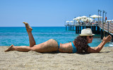 Beautiful girl lies on a sandy beach in a bathing suit sunbathing. Resort of the Mediterranean Sea. The girl in the sand. Turkey. - 208597912