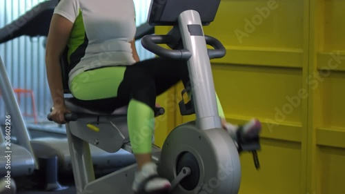 Poster Tilt up of sweaty middle-aged woman with red face training on cycling machine in gym
