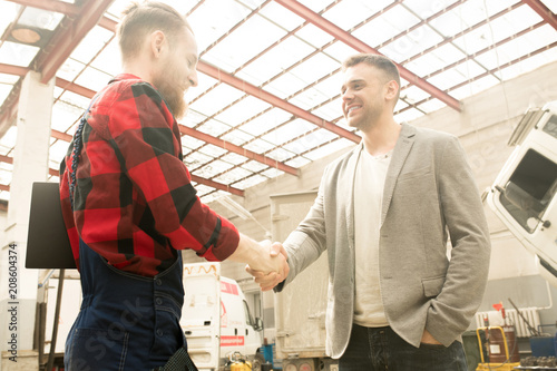 Low angle view of young handsome male car owner shaking hands with auto mechanic and smiling cheerfully after successful inspection