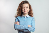 good-looking female teen in blue shirt with crossed arms. ambitious girl - 208623709