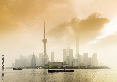 Fotobehang Shanghai Shanghai Financial Center and modern skyscraper city in misty gold lighting sunrise behind pollution haze, view from the bund in Shanghai, China. vintage picture style