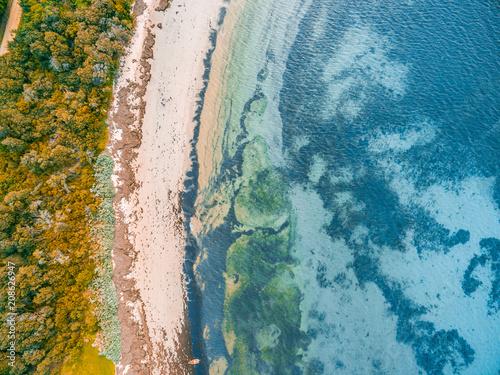 Fotobehang Groen blauw Looking down at shallow ocean water and rocky beach