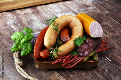 Leinwanddruck Bild Food tray with delicious salami, ham,  fresh sausages, cucumber and herbs. Meat platter
