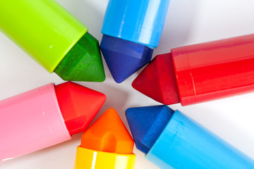Chunky colorful markers touching eachother making star shape closeup