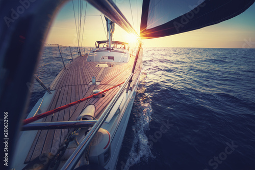 Fotobehang Zeilen Sunset at the Sailboat deck while cruising / sailing at opened sea. Yacht with full sails up at the end of windy day. Sailing theme - background. Yachting design.