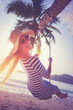 Leinwanddruck Bild - Young woman swinging on the beach and smiling into camera at sunset. Vacation concept. Retro styled colors.