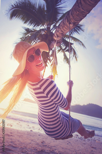 Leinwanddruck Bild Young woman swinging on the beach and smiling into camera at sunset. Vacation concept. Retro styled colors.