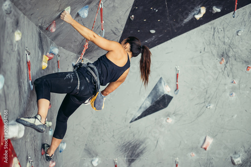 Leinwanddruck Bild Extreme sport, stress relief, bouldering, people and healthy lifestyle concept. Young sporty muscular woman climbing up on top of rock wall in gym, low angle, rear view.
