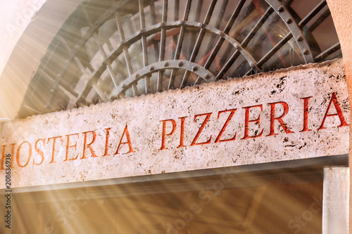Fotobehang Pizzeria The Hosteria Pizzeria sign above the entrance to the pizzeria is sunburned.