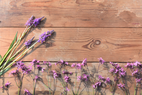 Fotobehang Lavendel pink and purple wildflowers on an old wooden background with larch boards, top view.