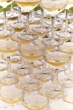Champagne glasses standing in a tower at a festive event, party or wedding reception. Champagne pyramid. - 208640104