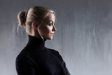 Portrait of beautiful blonde woman. Calm and self-confidence. Beautiful adult girl in black turtleneck, gray background - 208641994
