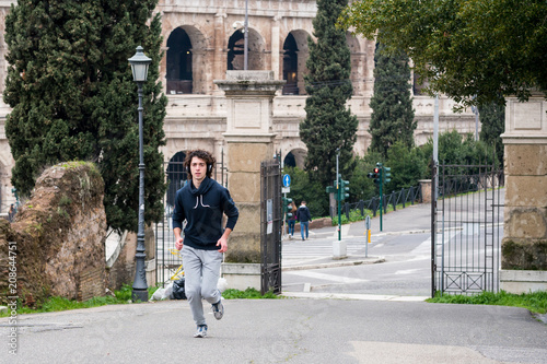 Fotobehang Hardlopen Handsome young sportsman jogging in park in Rome city