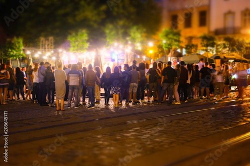 A crowd of people moving on the old european city night street defocused blurred abstract image - 208645711