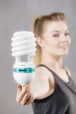 Woman holding eco modern light bulb - 208656103