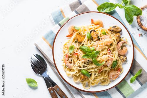 Fototapeta Pasta spaghetti with seafood and cream sauce on white.