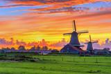 Traditional village at sunset, with dutch windmills, bridge and river on Zaanse Schans, Holland, Netherlands.