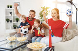 family of fans watching a football match on TV at home - 208659196
