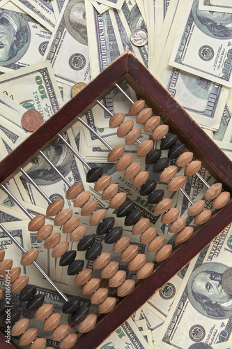 Old accounting wooden abacus on pile of money. US dollars and coins. Retro vintage old antique calculator. - 208660954