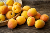 Ripe juicy apricots in a basket on a wooden background